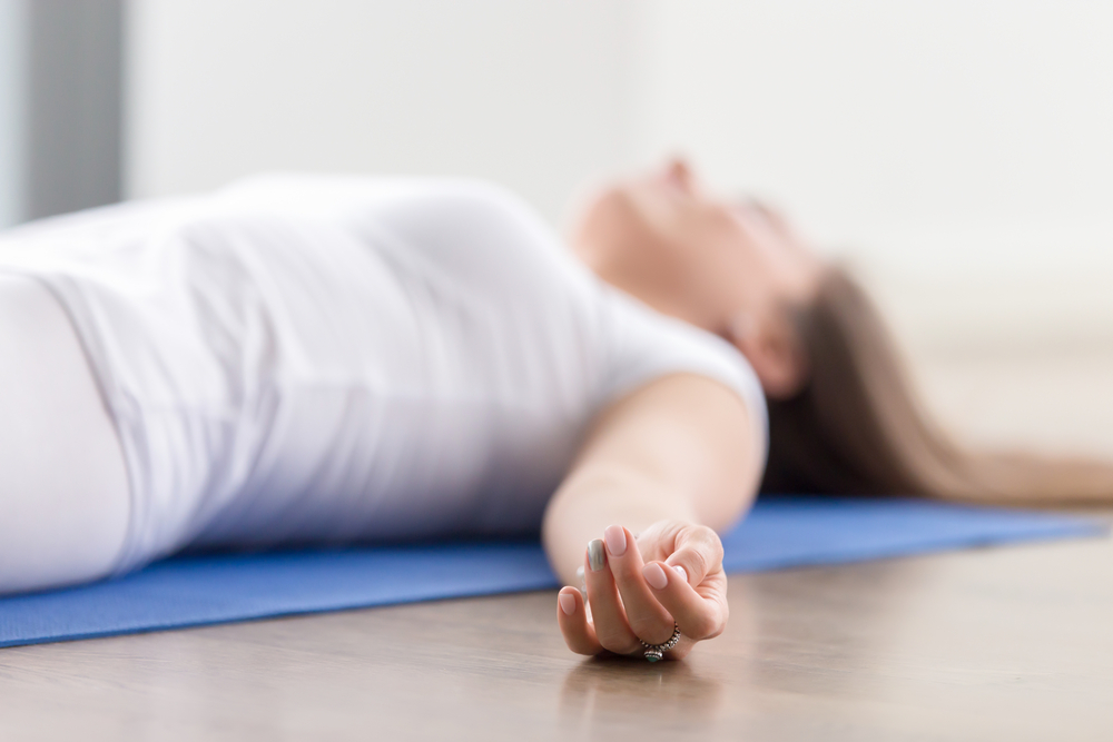 person in savasana practicing mindful fluidity